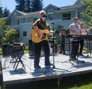 Lynnwood City Council candidate and lead vocalist for the band GenRASun, Jim Smith, providing entertainment at the car show.